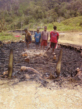 West Papuan children stare at the charred remains of their village after it was burnt down in an Indonesian military sweeping operation. 2010