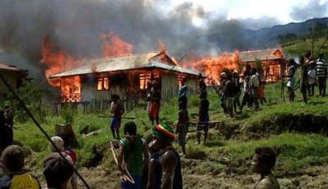 West Papuans return to their village after it is burnt by the Indonesian military